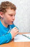 Il bambino fa il compito e rosicchia la penna Immagini Stock