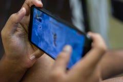 Il bambino facendo uso della tecnologia di modello del bambino di dipendenza dello smartphone esagera lo sguardo fotografia stock