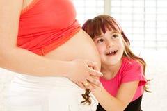 Il bambino felice abbraccia una madre incinta Fotografia Stock Libera da Diritti