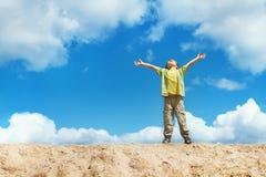 Il bambino felice che si leva in piedi con le mani si è alzato in su sopra il cielo Fotografia Stock
