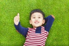 Il bambino felice che si trova ed alza il suo pollice Fotografie Stock Libere da Diritti