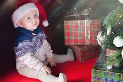Il bambino felice con i molti contenitore di regalo vicino ha decorato l'albero di Natale Immagine Stock