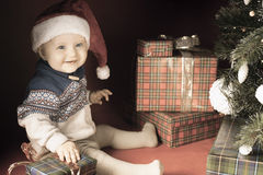 Il bambino felice con i molti contenitore di regalo vicino ha decorato l'albero di Natale Fotografia Stock Libera da Diritti