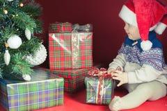 Il bambino felice con i molti contenitore di regalo vicino ha decorato l'albero di Natale Fotografia Stock