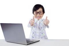 Il bambino felice con il computer portatile mostra il gesto di mani Fotografie Stock Libere da Diritti