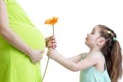Il bambino felice dà il fiore alla madre incinta fotografia stock libera da diritti