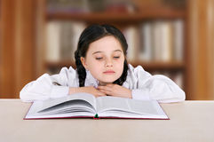 Il bambino felice della bambina legge il libro in biblioteca Immagine Stock Libera da Diritti