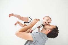 Il bambino felice della tenuta del padre nelle spese generali delle mani ha isolato il fondo Fotografia Stock