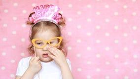 Il bambino felice divertente celebra il compleanno, si diverte, ride Ragazza sveglia del ritratto del primo piano su fondo rosa D video d archivio