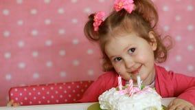 Il bambino felice divertente spegne le candele sulla torta di compleanno al partito Bambina sveglia Il concetto di una festa del  archivi video