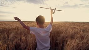 Il bambino felice funziona con un aeroplano del giocattolo su un fondo del tramonto sopra un giacimento di grano Fotografia Stock Libera da Diritti