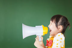 Il bambino felice grida qualcosa nel megafono Immagine Stock