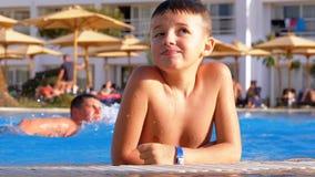 Il bambino felice nuota in uno stagno con acqua blu all'hotel Movimento lento video d archivio