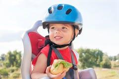 Il bambino felice (ragazzo) sta mangiando il pranzo (spuntino) durante il giro della bicicletta Fotografie Stock