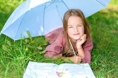 Il bambino felice si trova su erba sotto un ombrello immagine stock