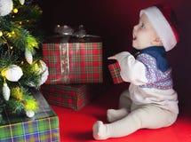 Il bambino felice vicino ha decorato l'albero di Natale con i molti contenitore di regalo Fotografia Stock