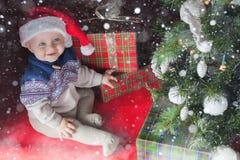 Il bambino felice vicino ha decorato l'albero di Natale con i molti contenitore di regalo Immagine Stock