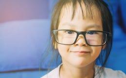 Il bambino femminile asiatico nerd sta leggendo un libro fotografia stock
