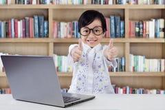 Il bambino femminile con il computer portatile mostra il gesto di mani Fotografia Stock