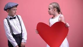 Il bambino femminile divertente con cuore di carta che prova a baciare il bambino maschio del giovane ragazzo retrocede la data fotografia stock