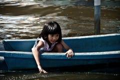 Il bambino femminile si siede sulla barca di plastica Fotografia Stock Libera da Diritti