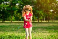 Il bambino femminile sveglio prende le bolle di sapone in natura fotografia stock