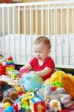 Il bambino gioca i giocattoli contro il letto bianco Fotografia Stock Libera da Diritti