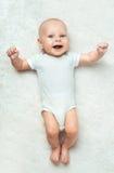 Il bambino grazioso sta trovandosi sul tappeto Immagine Stock