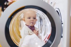 Il bambino guarda attraverso la finestra della lavatrice immagini stock libere da diritti