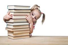 Il bambino guarda fuori da dietro i libri Immagini Stock