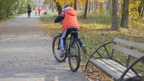 Il bambino guida la grande bici il ragazzo spinge il suo piede fuori dal banco Sostegni per banchi in un parco della città Il rag stock footage