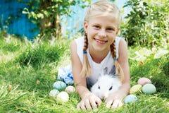 Il bambino ha cercato sull'uovo di Pasqua nel giardino di fioritura della molla fotografie stock