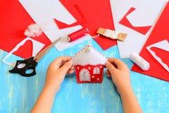 Il bambino ha fatto un ornamento della casa sull'albero di Natale di feltro rosso e bianco Il bambino tiene l'ornamento della cas Fotografie Stock Libere da Diritti