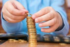 Il bambino ha raccolto il grande mucchio delle monete di oro, primo piano Immagini Stock