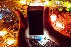 Il bambino ha trovato un regalo sotto forma di smartphone bianco fotografie stock
