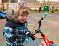 Il bambino ha visto la bicicletta ad un campo da giuoco, è sorpreso e adm Immagine Stock