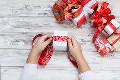 Il bambino imballa un regalo fatto a mano Regali di Natale, Immagine Stock