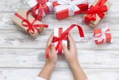 Il bambino imballa un regalo fatto a mano Regali di Natale, Fotografia Stock