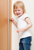 Il bambino impertinente sta levandosi in piedi nell'angolo immagine stock libera da diritti
