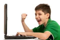 Il bambino impressionabile sta giocando il gioco di computer immagini stock