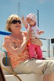 Il bambino indica alla vela mentre si siede su una barca a vela Fotografie Stock