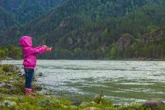 Il bambino lancia una barca di carta in un fiume montagnoso Fotografie Stock