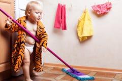 Il bambino lava il pavimento Fotografia Stock
