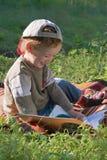 Il bambino legge il libro e sorride Immagine Stock Libera da Diritti