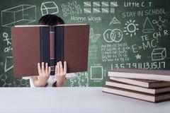 Il bambino legge seriamente i manuali nella classe Immagine Stock Libera da Diritti