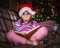 Il bambino legge un libro al Natale Immagini Stock Libere da Diritti
