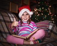 Il bambino legge un libro al Natale Fotografie Stock