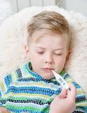 Il bambino malato con febbre alta che si situano a letto e la madre controlla il tem Immagine Stock Libera da Diritti