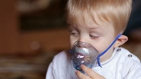 Il bambino malato respira tramite il nebulizzatore, primo piano video d archivio