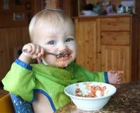 Il bambino mangia con una quinoa del cucchiaio con le verdure Immagine Stock